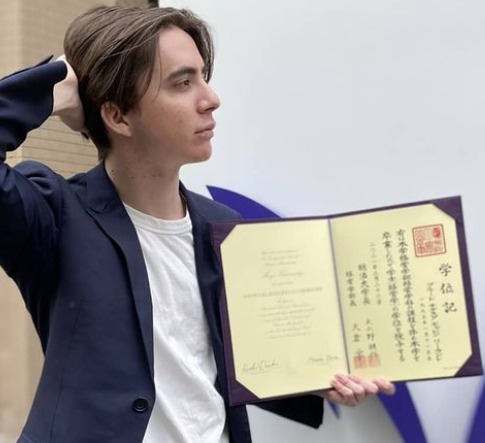 ギャビンが明治大学の卒業証書を持っているところ